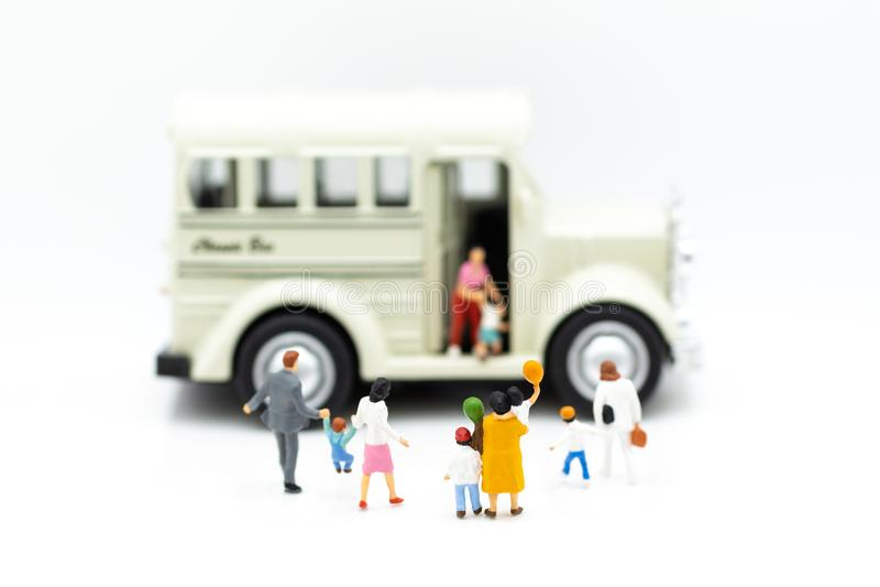 Familia miniatura: Los padres van a enviar a niños al autobús para van a la escuela Uso de la imagen para el concepto de la educa foto de archivo libre de regalías