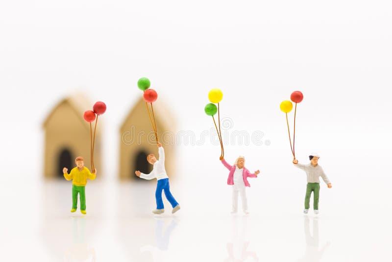 Familia miniatura ni os que sostienen el globo colorido for Concepto de la familia para ninos