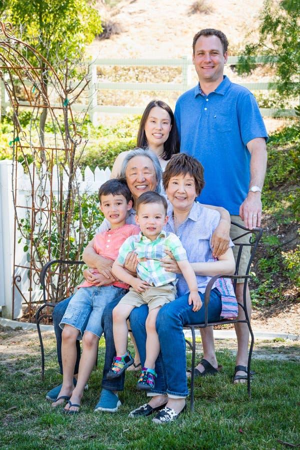 Familia multiétnica caucásica china que se sienta en banco foto de archivo