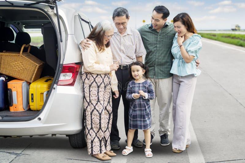 Familia multi de la generación con el coche en el camino foto de archivo