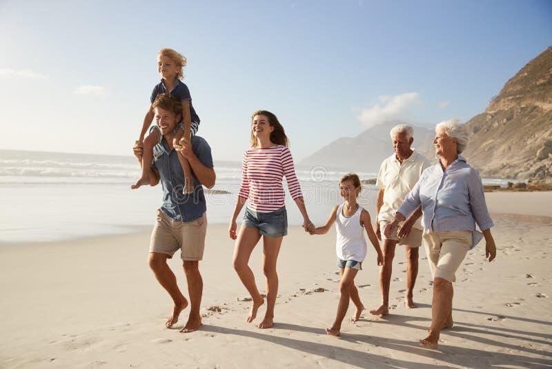Familia multi de la generación el vacaciones que camina a lo largo de la playa junto imagenes de archivo