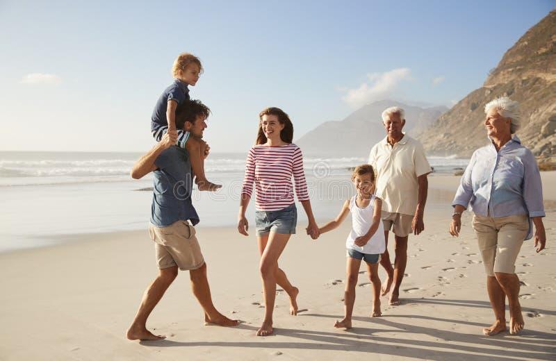 Familia multi de la generación el vacaciones que camina a lo largo de la playa junto imágenes de archivo libres de regalías