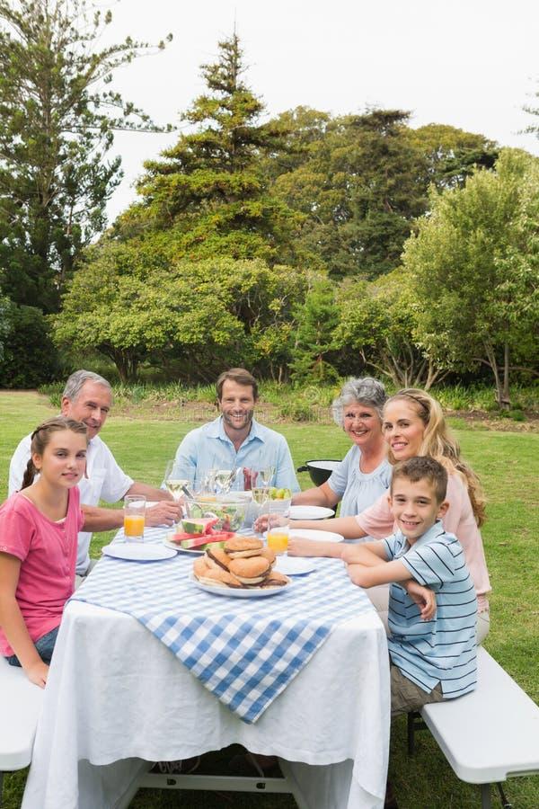 Familia multi de la generación en la mesa de picnic que cena afuera imágenes de archivo libres de regalías