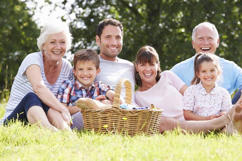 Familia multi de la generación que disfruta de comida campestre en campo imágenes de archivo libres de regalías