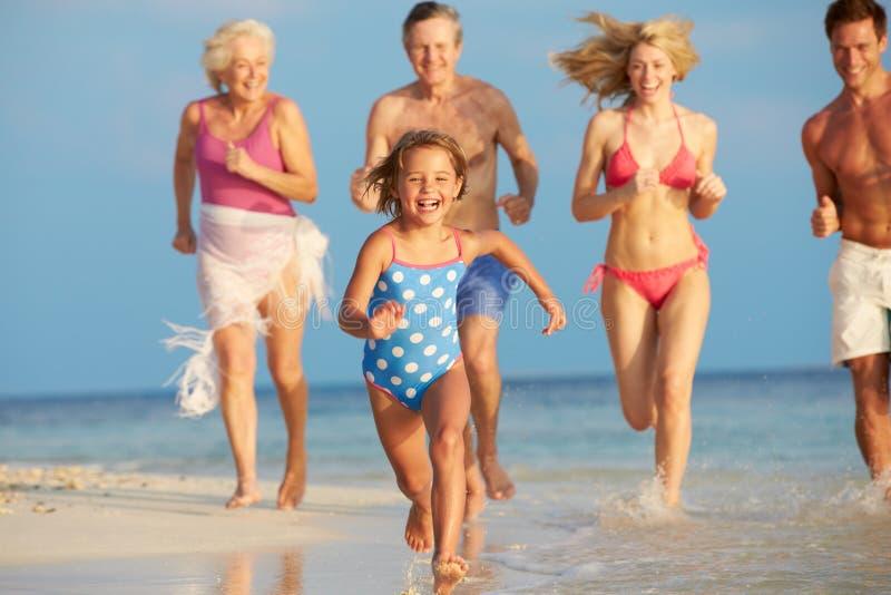 Familia multi de la generación que se divierte en el mar el día de fiesta de la playa imagenes de archivo