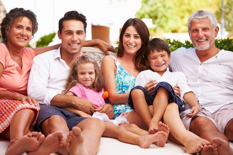 Familia multi de la generación que se sienta al aire libre en casa junto imagenes de archivo