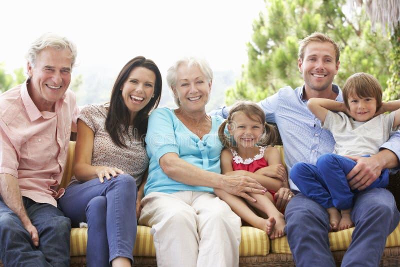 Familia multi de la generación que se sienta en el jardín Seat foto de archivo libre de regalías