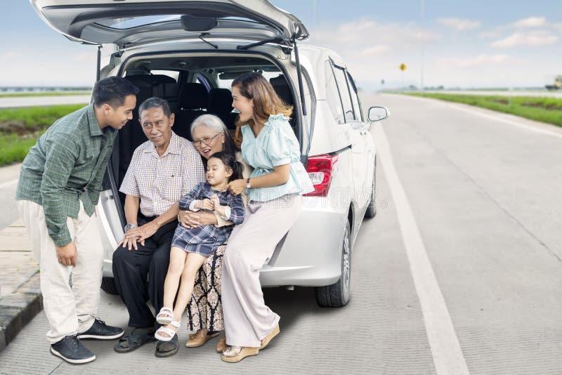 Familia multi de la generación que se sienta en el tronco de coche fotos de archivo libres de regalías