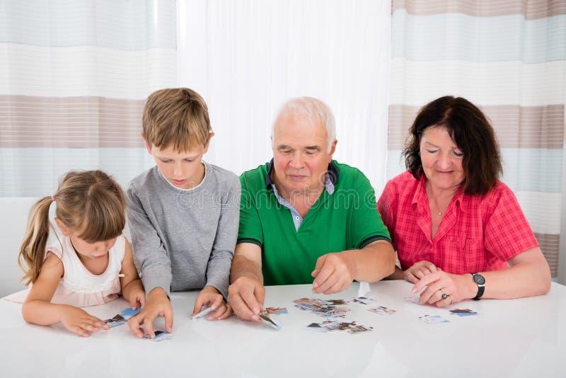 Familia multi de la generación que soluciona rompecabezas junto foto de archivo libre de regalías