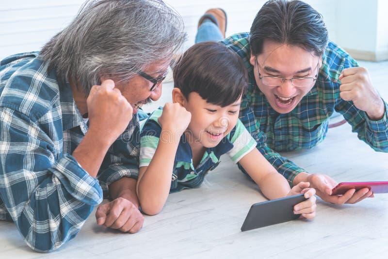 Familia multi de la generación que tiene éxito usando tecnología móvil de Internet imágenes de archivo libres de regalías