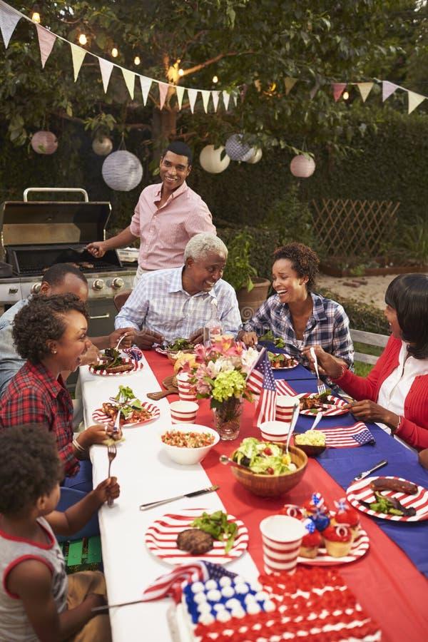 Familia multi del negro de la generación en la barbacoa del 4 de julio, vertical imagenes de archivo