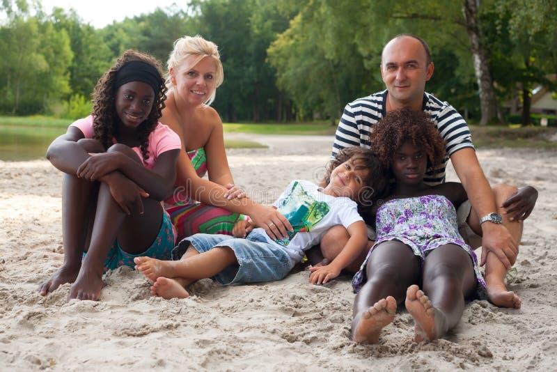 Familia multicultural en la playa fotos de archivo