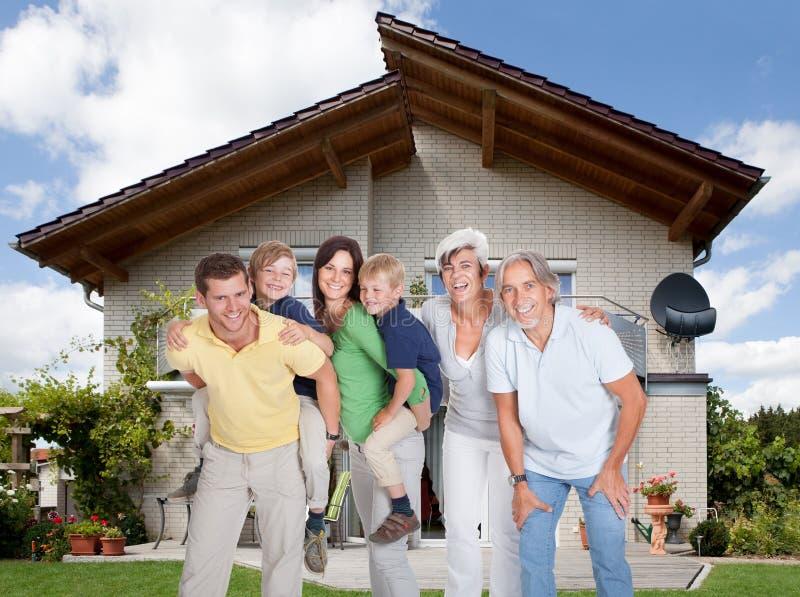 Familia multigeneración delante de la casa imágenes de archivo libres de regalías