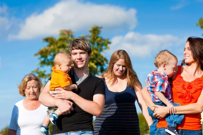 Familia multigeneración en prado en verano