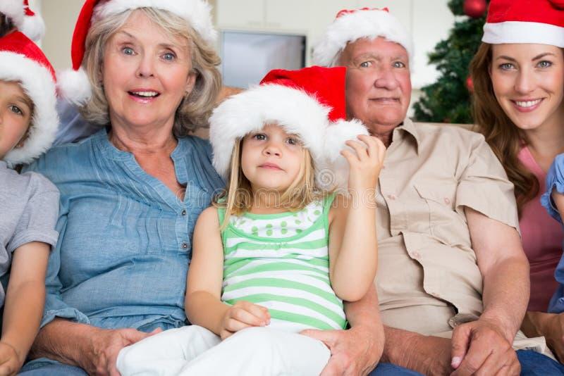 Familia multigeneración feliz que lleva los sombreros de santa en el sofá fotografía de archivo