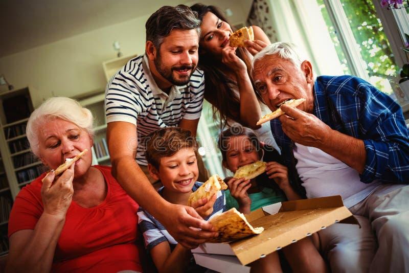 Familia multigeneración que come la pizza junta imagen de archivo libre de regalías