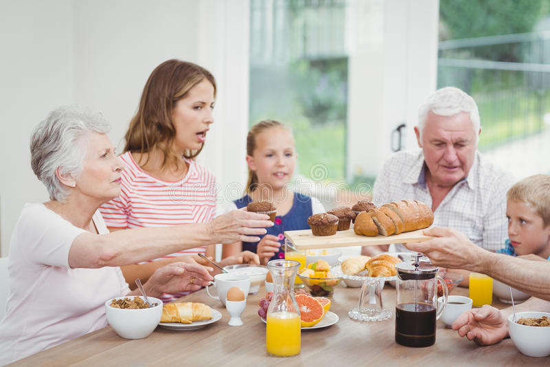 Familia multigeneración que come molletes durante el desayuno imagenes de archivo
