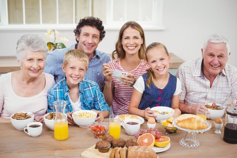 Familia multigeneración que desayuna en casa imagenes de archivo