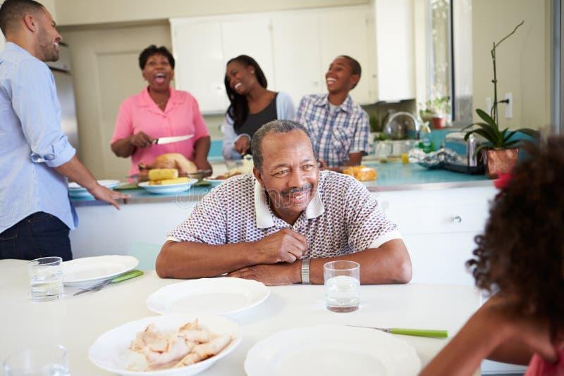 Familia multigeneración que se prepara para la comida en casa imagen de archivo