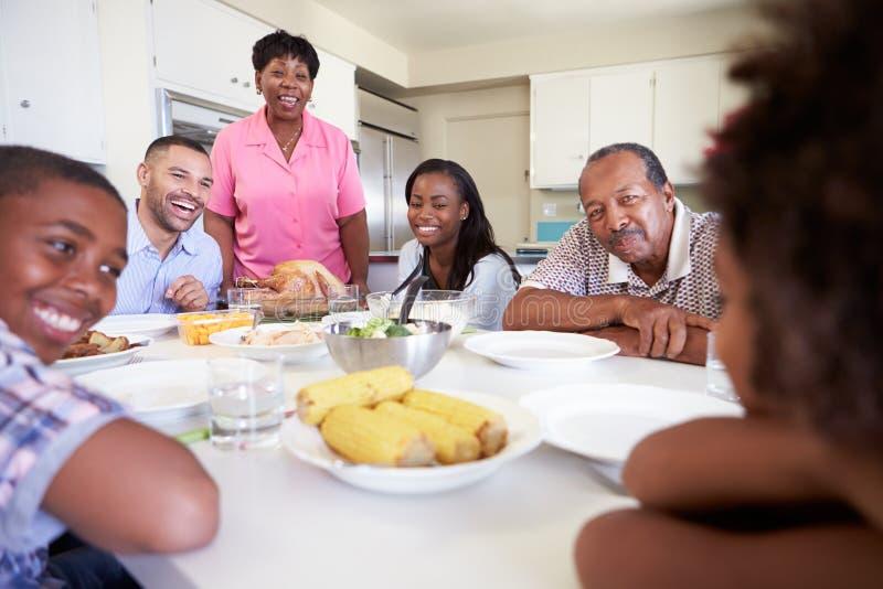 Familia multigeneración que se sienta alrededor de la tabla que come la comida imágenes de archivo libres de regalías
