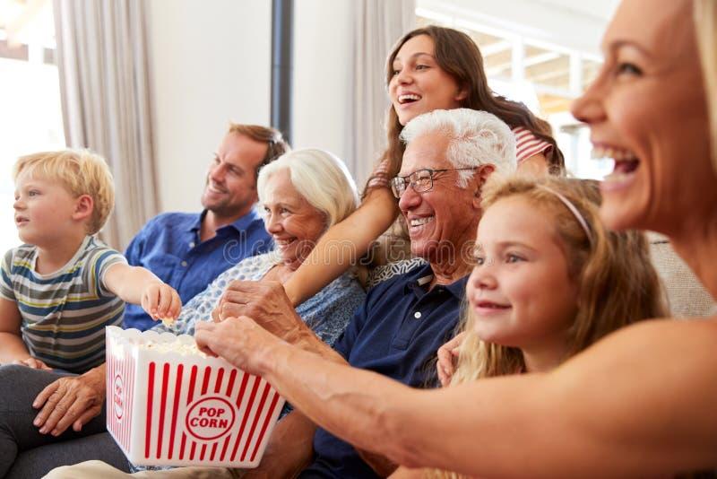 Familia multigeneración que se sienta en Sofa At Home Eating Popcorn y película de observación junto imágenes de archivo libres de regalías
