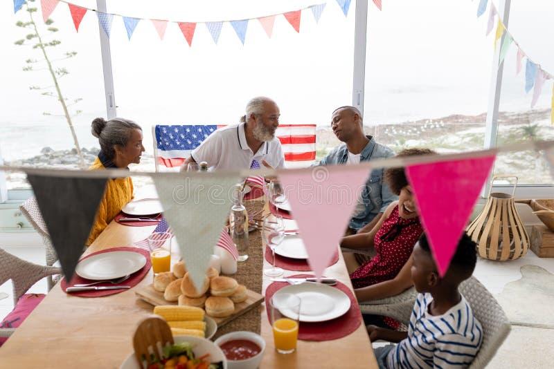 Familia multigeneración que se sienta junto para tener comida en una mesa de comedor imagenes de archivo
