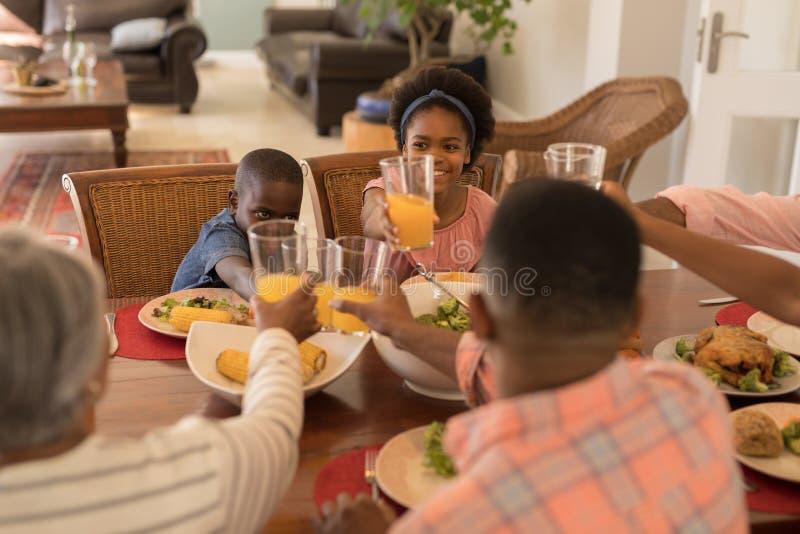 Familia multigeneración que tuesta los vidrios de zumo de naranja en la mesa de comedor foto de archivo libre de regalías