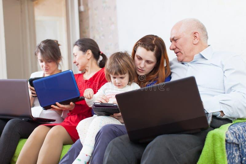 Familia multigeneración usando los ordenadores portátiles fotos de archivo