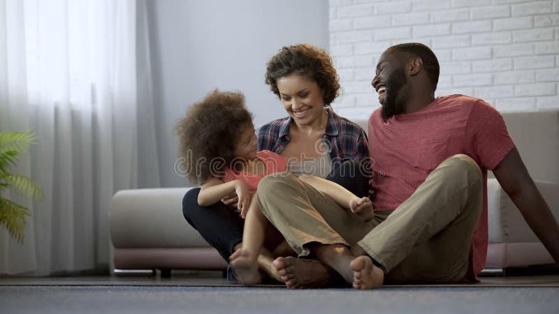 Familia multirracial que se sienta junto y que ríe, pasando el tiempo agradable junto fotos de archivo