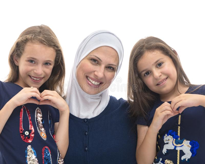Familia musulmán feliz, madre y sus hijas con el gesto de mano de la muestra del amor de la mamá imagenes de archivo