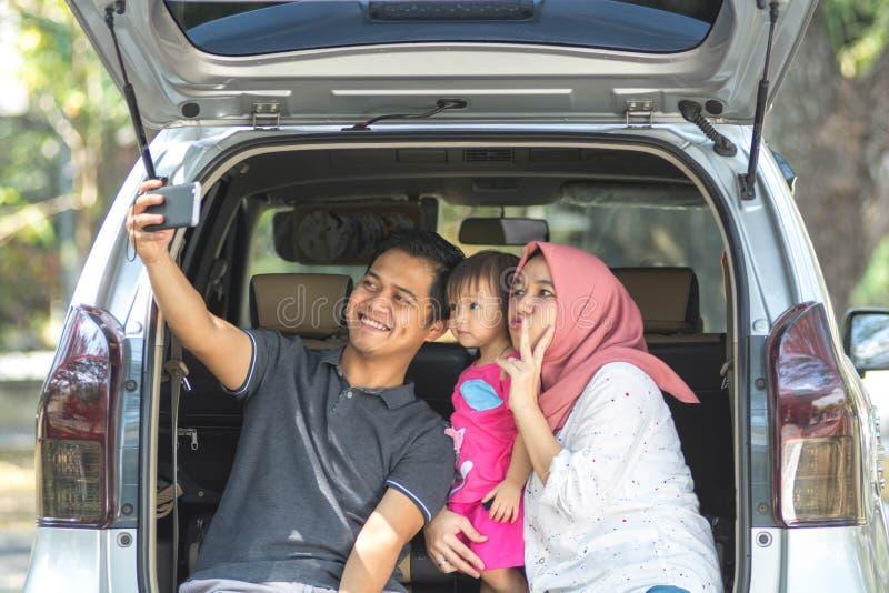 Familia musulmán joven, transporte, ocio, viaje por carretera y concepto de la gente - vista delantera del hombre, de la mujer fe imagenes de archivo