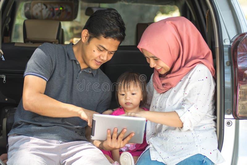 Familia musulmán joven, transporte, ocio, viaje por carretera y concepto de la gente - vista delantera del hombre, de la mujer fe fotos de archivo libres de regalías
