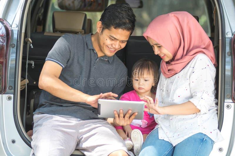 Familia musulmán joven, transporte, ocio, viaje por carretera y concepto de la gente - vista delantera del hombre, de la mujer fe imagen de archivo