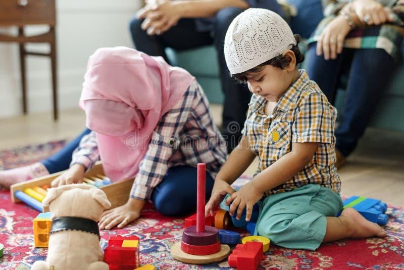 Familia musulmán que se relaja y que juega en casa fotografía de archivo