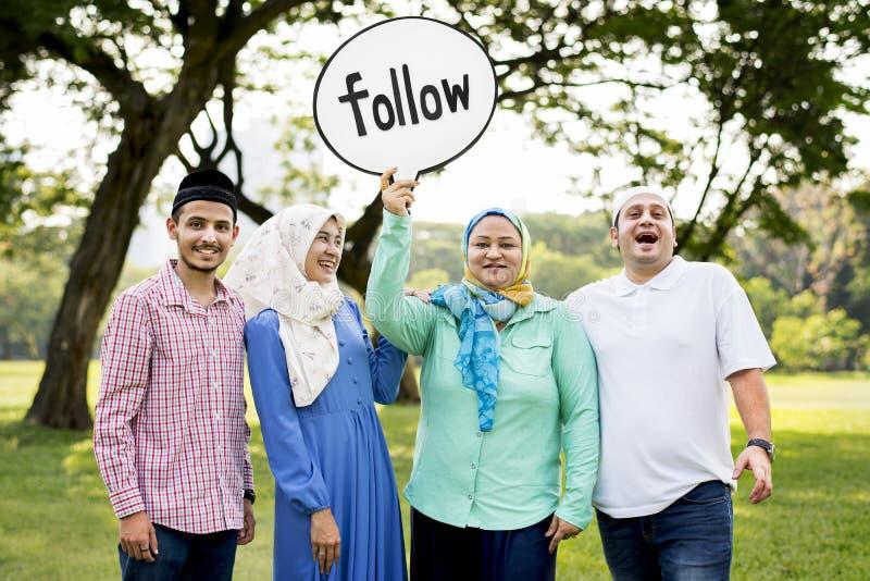 Familia musulmán que soporta una muestra del siguiente foto de archivo libre de regalías