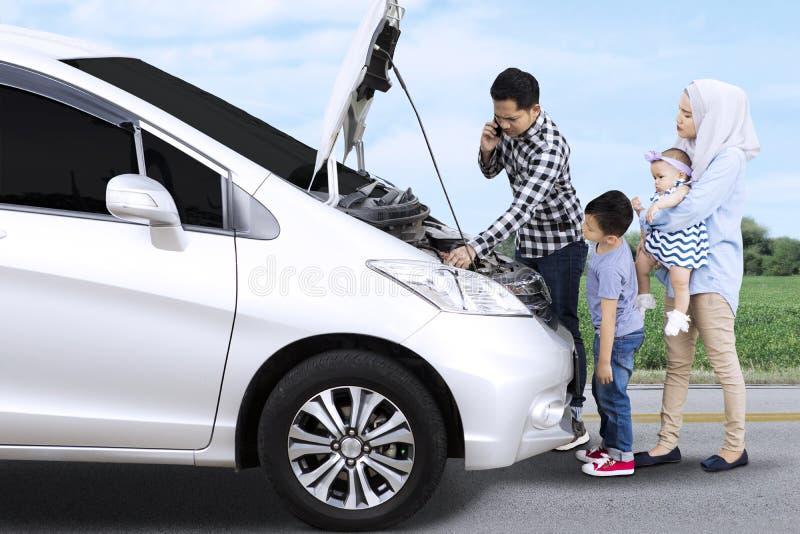 Familia musulmán que tiene problema con el coche quebrado fotografía de archivo