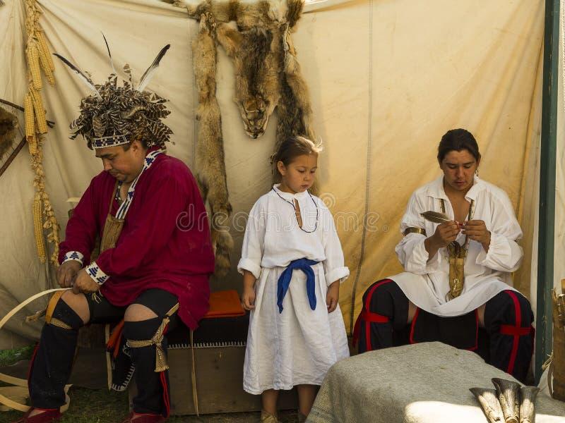 Familia nativa que participa en una demostración de artes tradicionales imagen de archivo libre de regalías