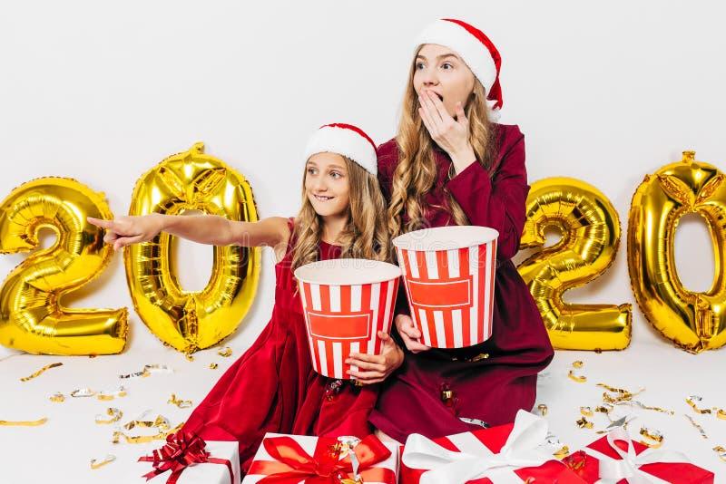 Familia navideña, madre e hija con sombreros de Santa sosteniendo cajas de palomitas, conmocionada al ver una película sentada c fotografía de archivo