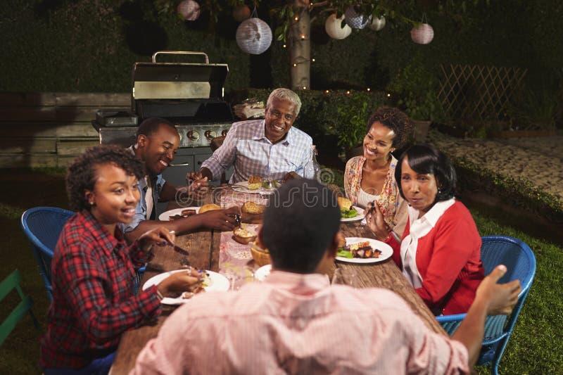 Familia negra adulta que habla en la cena en su jardín imagen de archivo libre de regalías