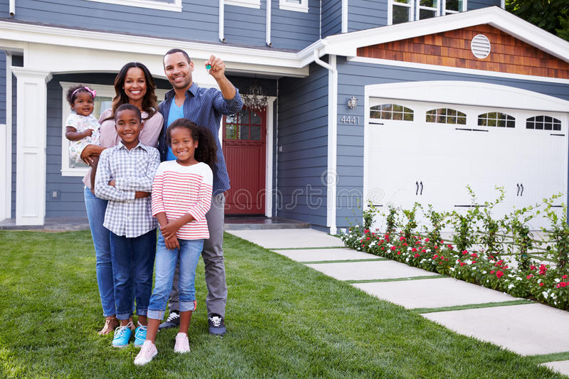 Familia negra feliz derecha fuera de su casa, papá que lleva a cabo la llave fotos de archivo libres de regalías