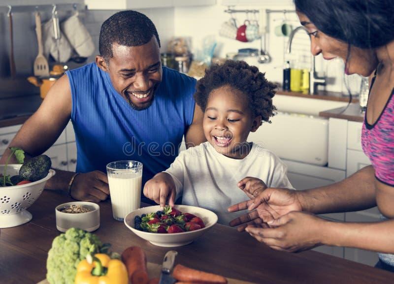 Familia negra que come la comida sana junta imagen de archivo