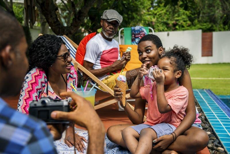Familia negra que disfruta del verano junto en el patio trasero imagenes de archivo