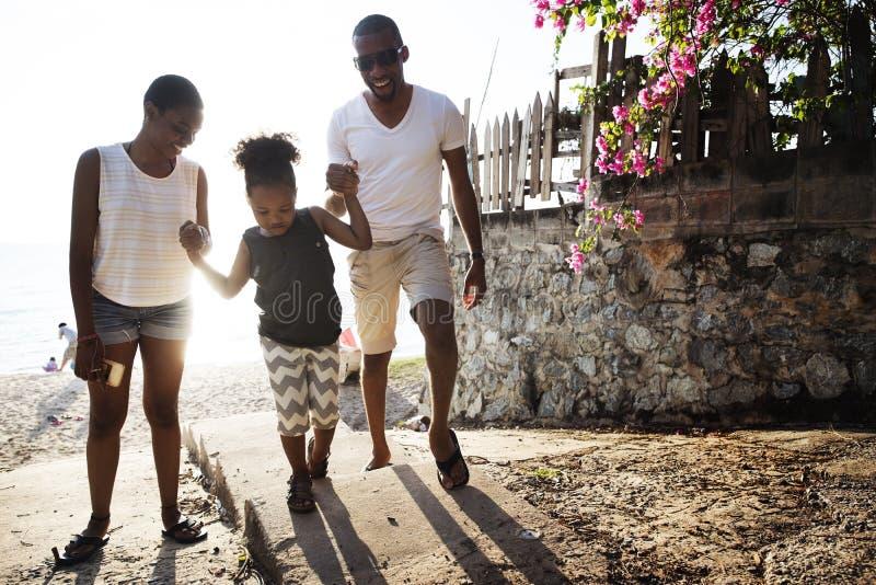 Familia negra que disfruta del verano junto en la playa imagen de archivo