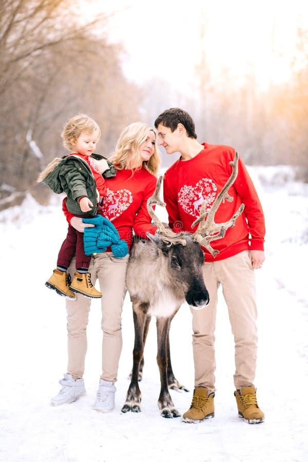 Familia, niñez, estación, días de fiesta y familia feliz del concepto de la gente en ropa del invierno sobre fondo de las luces foto de archivo libre de regalías