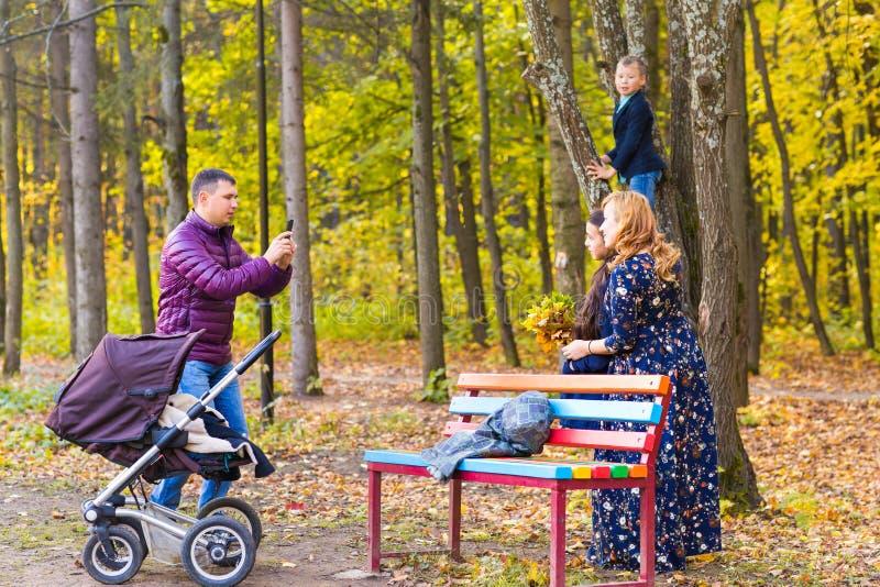 Familia, niñez, estación, tecnología y concepto de la gente - familia feliz que fotografía en parque del otoño imagen de archivo