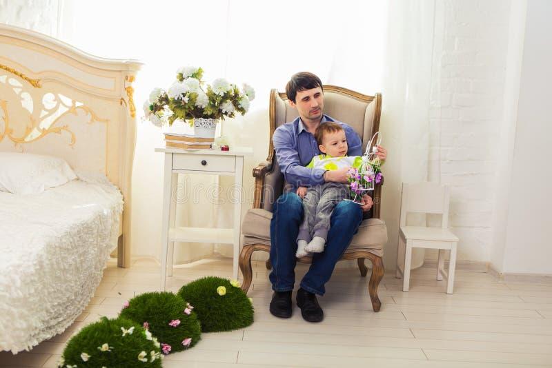 Familia, niñez, paternidad, actividad y concepto de la gente - padre feliz y pequeño hijo que juegan en casa fotografía de archivo