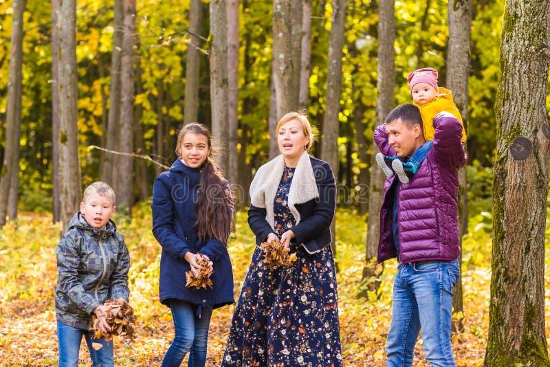 Familia, otoño, felicidad y concepto de la gente - la madre, el padre, el hijo y la hija jugando en otoño parquean imagen de archivo