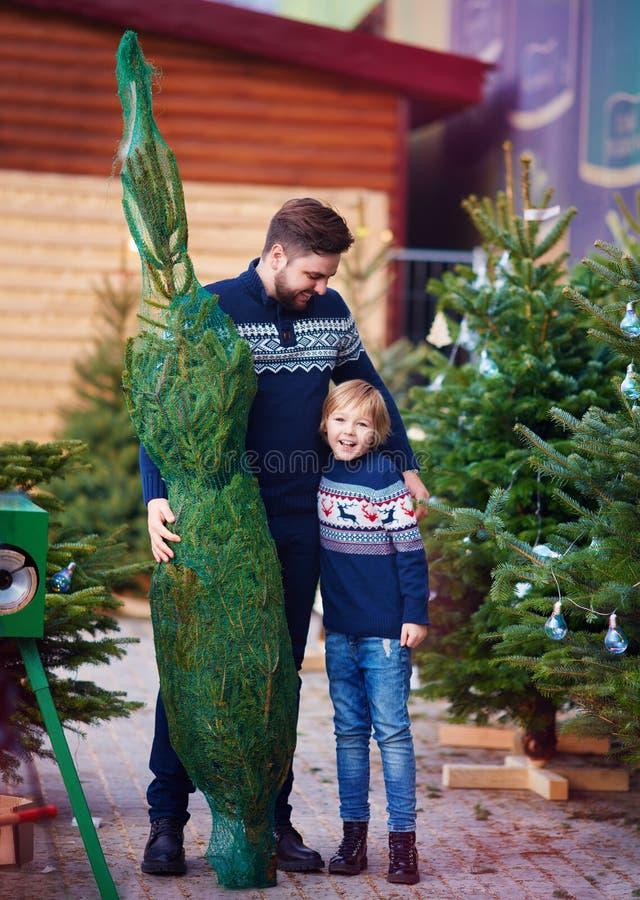Familia, padre feliz e hijo comprando un árbol de navidad por vacaciones de invierno en el mercado estacional foto de archivo