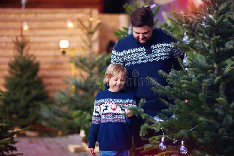 Familia, padre feliz e hijo comprando un árbol de navidad por vacaciones de invierno en el mercado estacional fotografía de archivo