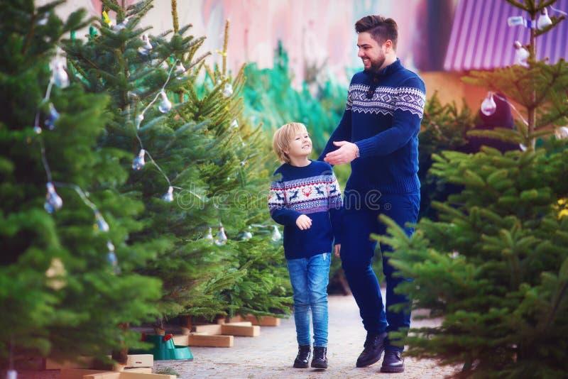 Familia, padre feliz e hijo eligiendo el árbol de navidad por vacaciones de invierno en el mercado estacional foto de archivo libre de regalías
